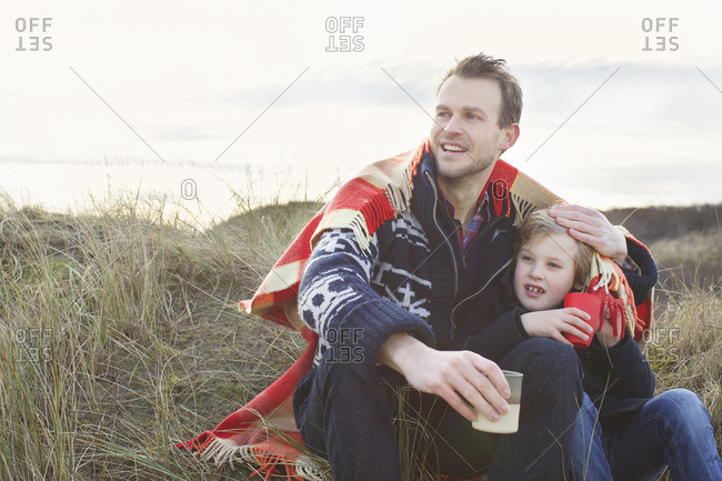 Smiling mid adult man and son on sand dunes