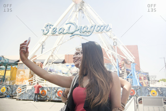 Los Angeles, california, USA - March 24, 2013: Two women at fairground, taking self portrait with smart phone