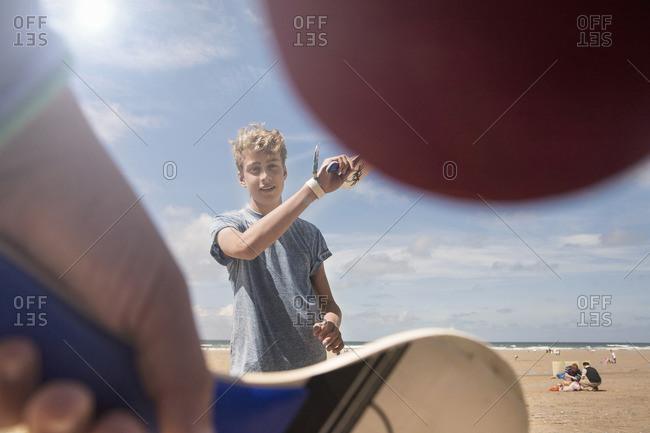 Teenage boy playing bat and ball on beach