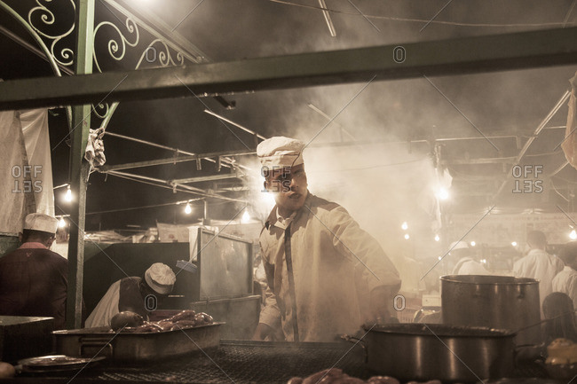 Chef cooking on restaurant stall at night, Jamaa el Fna , Marrakech, Morocco