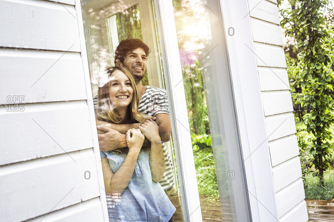 Young couple looking out of patio window