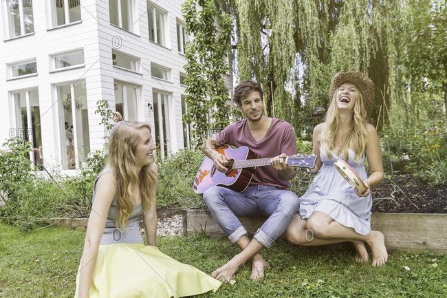 Three friends in garden, man playing guitar