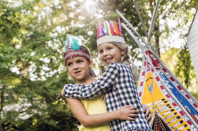 Two girls in native American headdress hugging in garden