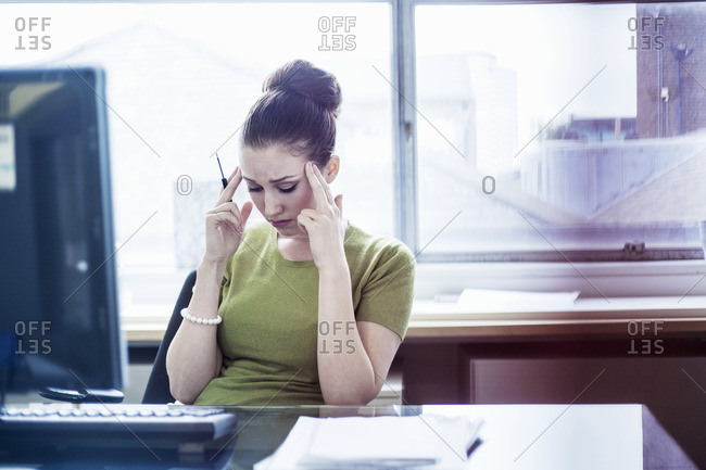 Young woman looking worried at her desk
