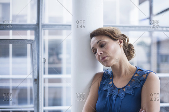 Woman leaning against pillar