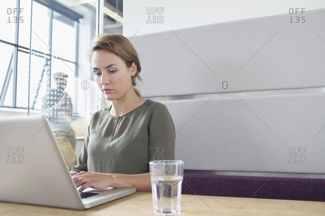 Young woman typing on laptop in office