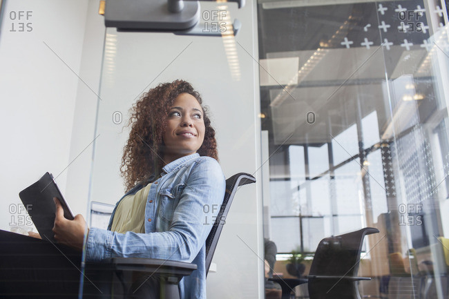 Portrait of young woman looking over her shoulder from office desk