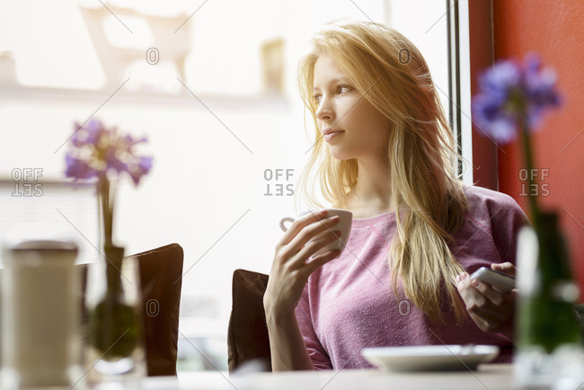 Young woman gazing out of cafe window whilst drinking coffee