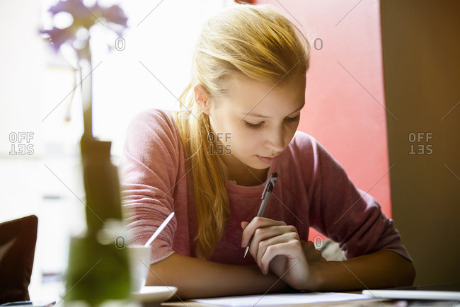 Young woman writing in note book at cafe table