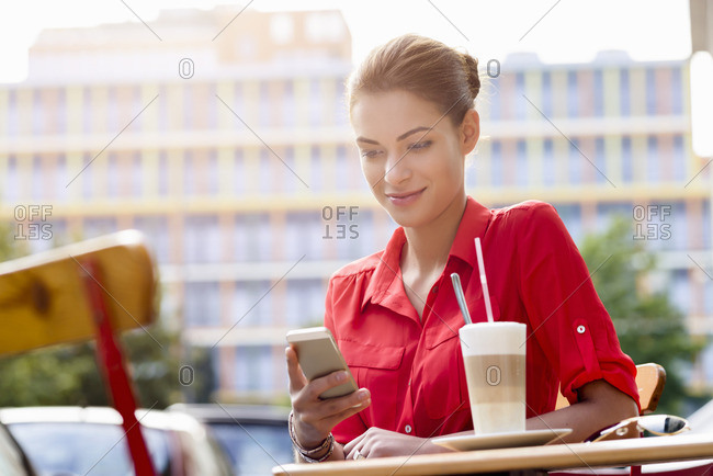 Young woman sitting outside cafe, using mobile phone