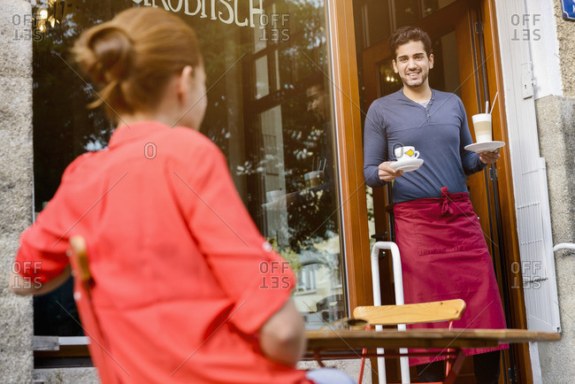 Young woman sitting outside cafe, cafe worker bringing drinks out