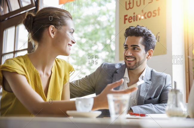 Young couple sitting inside cafe, talking, low angle view