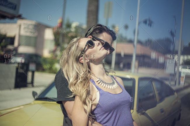 Young romantic couple, leaning against car
