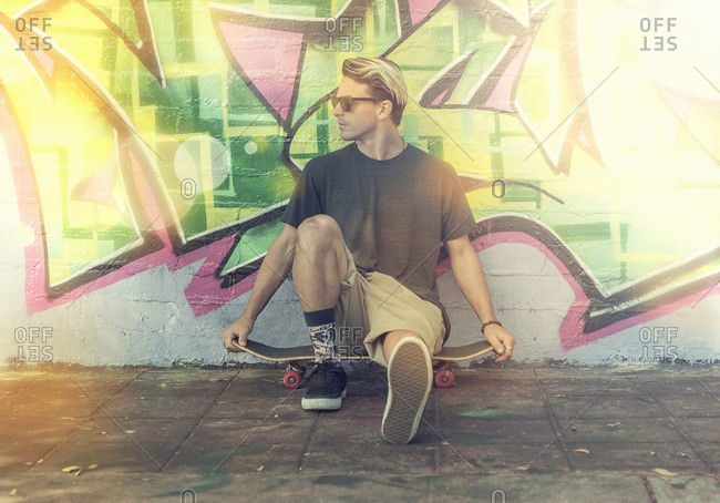 Young man sitting on skateboard, leaning against graffitied wall