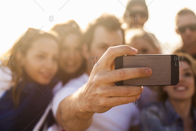 Group of friends taking selfie on beach