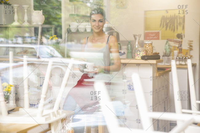 Young waitress sitting in cafe, view through window