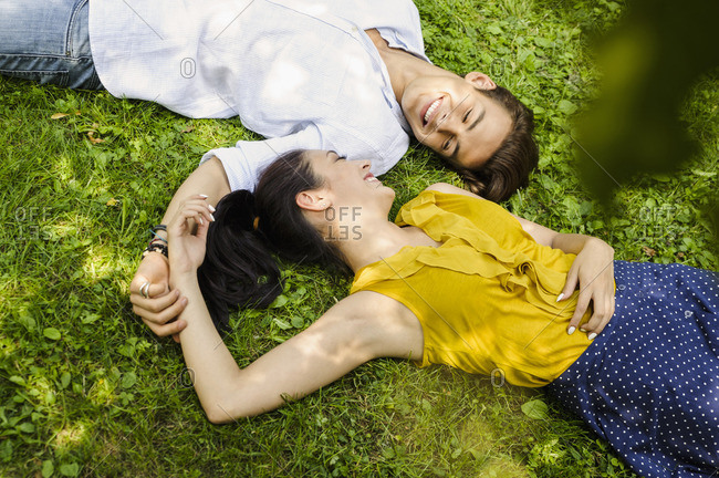 High angle view of young couple lying on grass