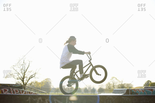 Young man doing stunt on bike at skatepark
