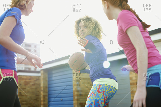 Portrait of three women exercising together playing basketball