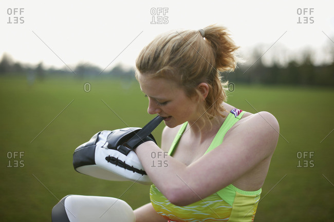 Portrait of a woman putting on boxing pads in the park
