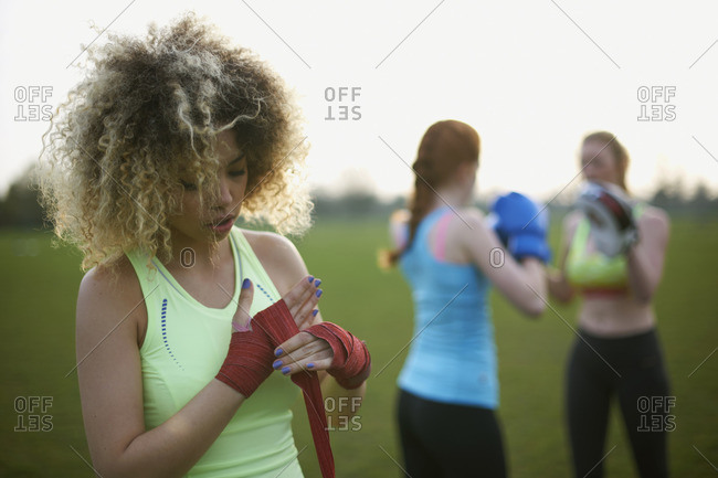 Three women exercising with boxing gloves in the park