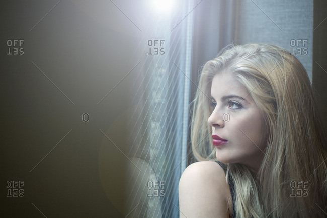 Close up portrait of beautiful blond young woman looking through hotel window