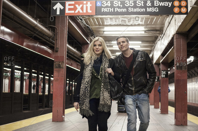 Romantic young couple strolling arm in arm on New York City subway platform, New York, USA