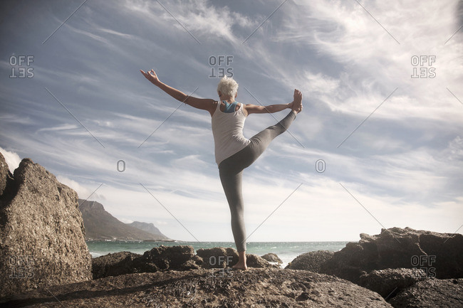 Woman practicing yoga by ocean, Cape Town, South Africa