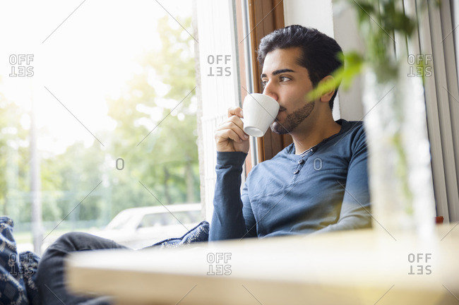 Young man sitting in front of window drinking coffee, looking away