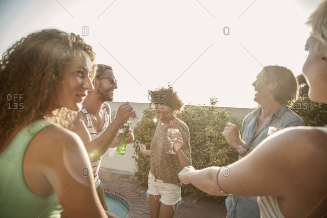 Adult friends drinking and dancing at poolside party