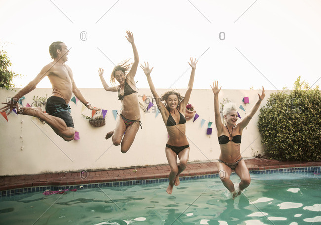 Mid adult man and three young women jumping into swimming pool at poolside party