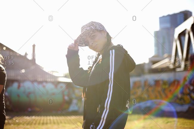 Side view of young woman wearing baseball cap, looking at camera