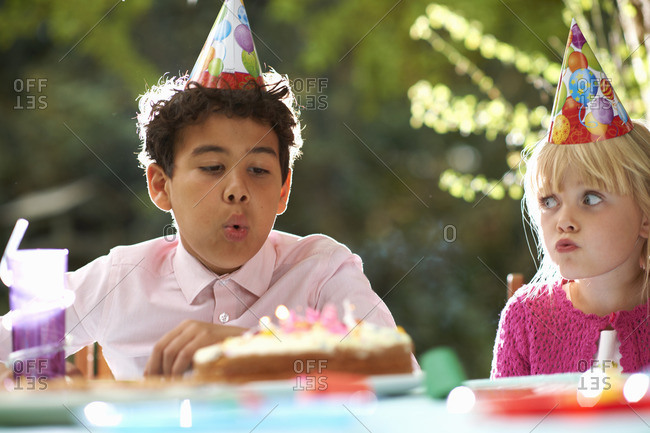 Boy blowing candles on birthday cake at garden birthday party