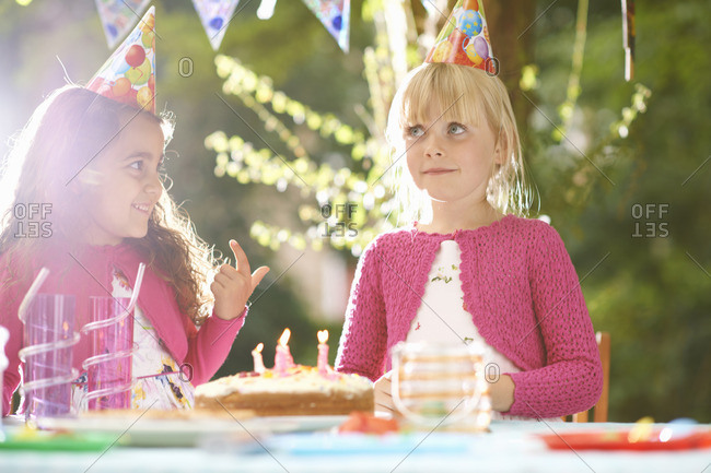 Girls with finger in birthday cake at garden birthday party