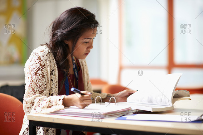 Young female student writing in file