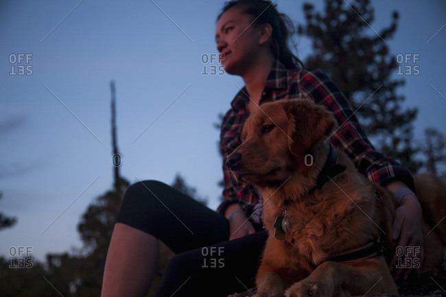 Low angle view of young woman sitting with arm around dog looking away