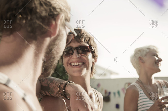 Couple wearing sunglasses face to face, arm on shoulder smiling