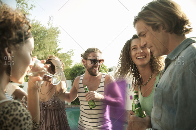 Small group of friends standing holding drinks talking and smiling, lens flare