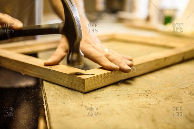 Wood artist working in workshop, using hammer, close-up