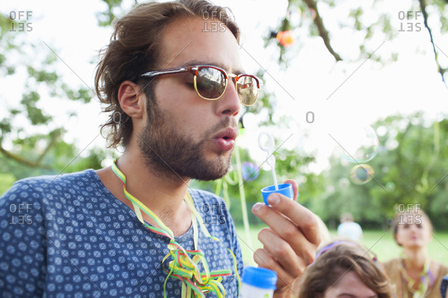 Young man blowing bubbles at sunset party in park