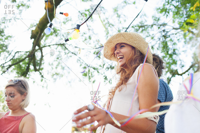 Young adult friends wrapped in streamers at sunset party in park