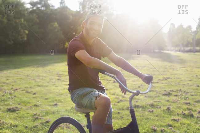Portrait of young man on bicycle in sunlit park