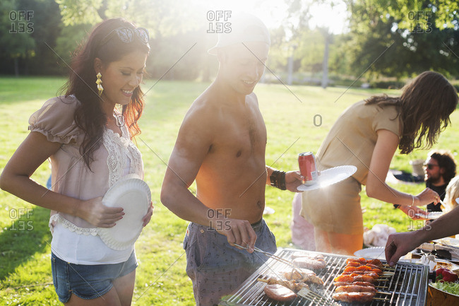 Group of friends barbecuing at sunset park party