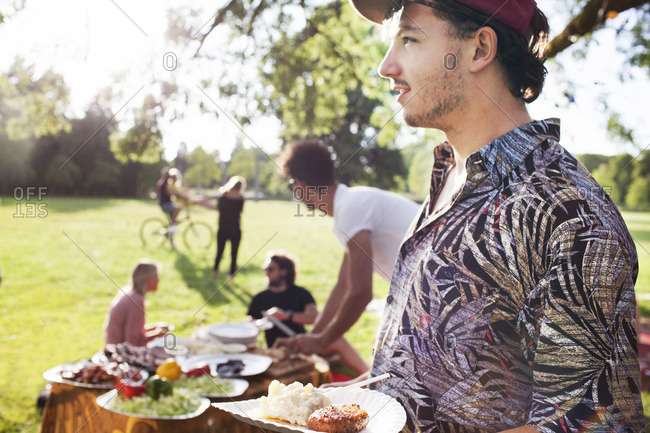 Young man with plate of picnic food at park party