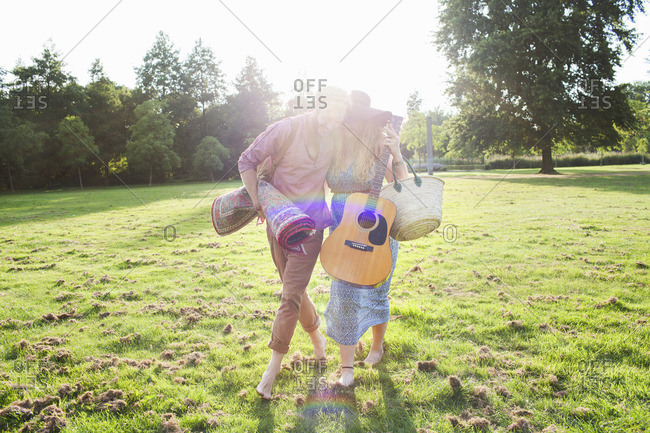 Romantic young couple carrying rug in park