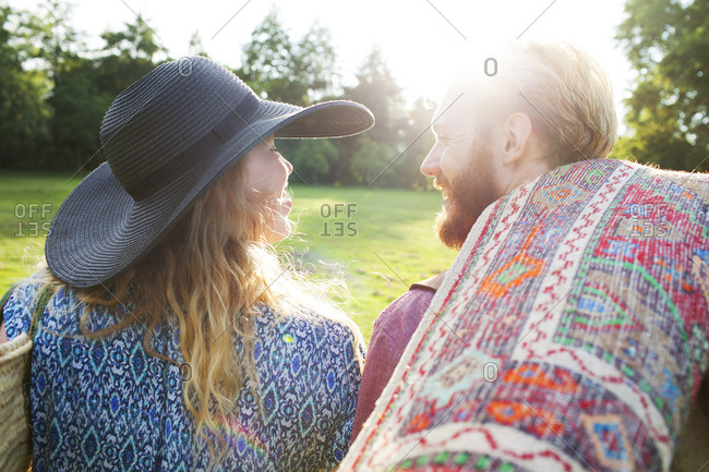 Rear view of romantic young couple carrying rug for picnic in park