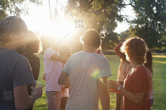 Adult friends partying and drinking in park at sunset