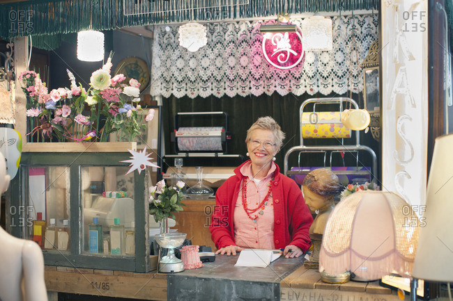 Portrait of mature woman behind vintage shop counter