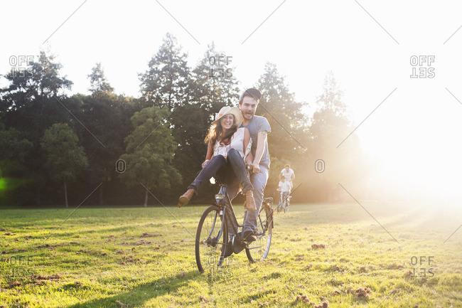 Young woman on handlebars of boyfriends bicycle at party in park