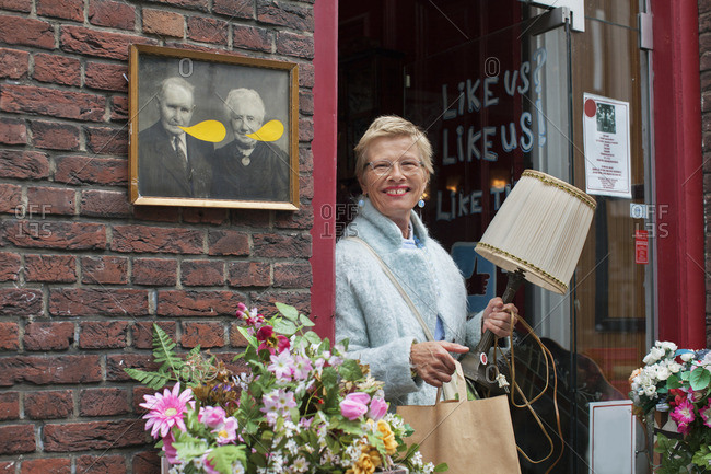 Mature female customer carrying lamp and shopping bag outside vintage shop